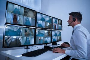 51450584-rear-view-of-security-system-operator-looking-at-cctv-footage-at-desk-in-office